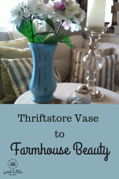 Beautiful farmhouse vase on a table with a candlestick , and glass bird.